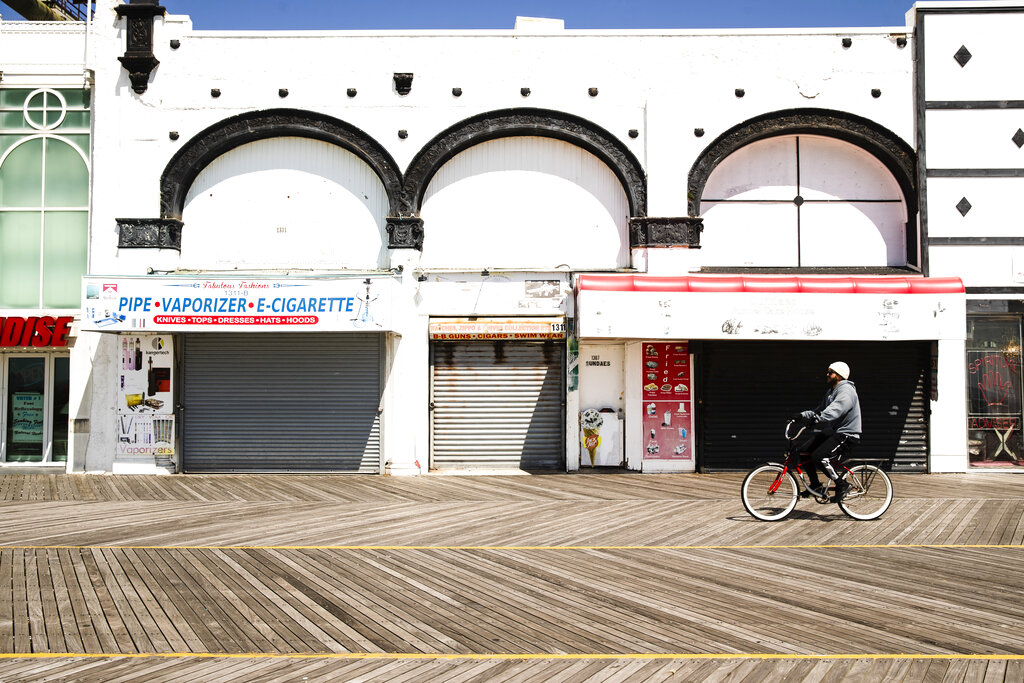 A cyclist rides past shuttered businesses during the coronavirus outbreak on the boardwalk in Atlantic City, N.J., Tuesday, April 28, 2020. (AP Photo/Matt Rourke)