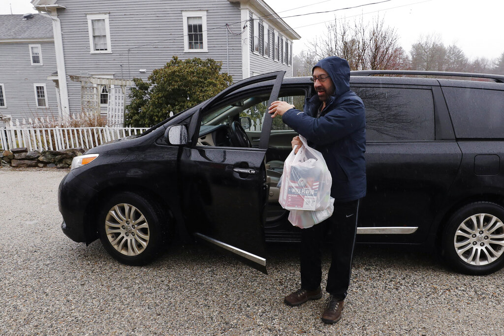 Instacart worker Arthur Berte delivers groceries to a home in East Derry, N.H. Some app-based delivery companies have announced hiring sprees, including Instacart, to cope with a surge in orders from millions of people stuck at home. (AP Photo/Charles Krupa, File)