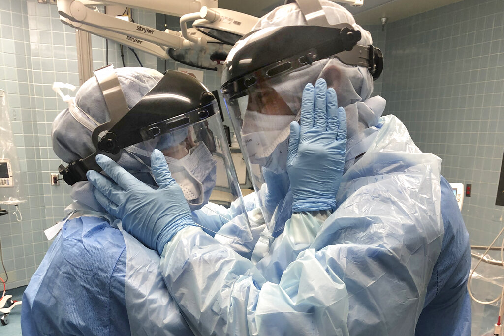 """Nurses Mindy Brock and Ben Cayer, wearing protective equipment, hold each other and look into each other's eyes in Tampa General Hospital in Tampa, Fla. """"Everybody's talking about the photo,"""" says Cayer, 46. It strikes a chord """"because we're all going through the same thing right now and it's a symbol of hope and love."""" Brock, 38, adds: """"What's important is that we stick together, we work together, and we always support each other. And not just Ben and I, but the human race right now."""" (Nicole Hubbard via AP)"""