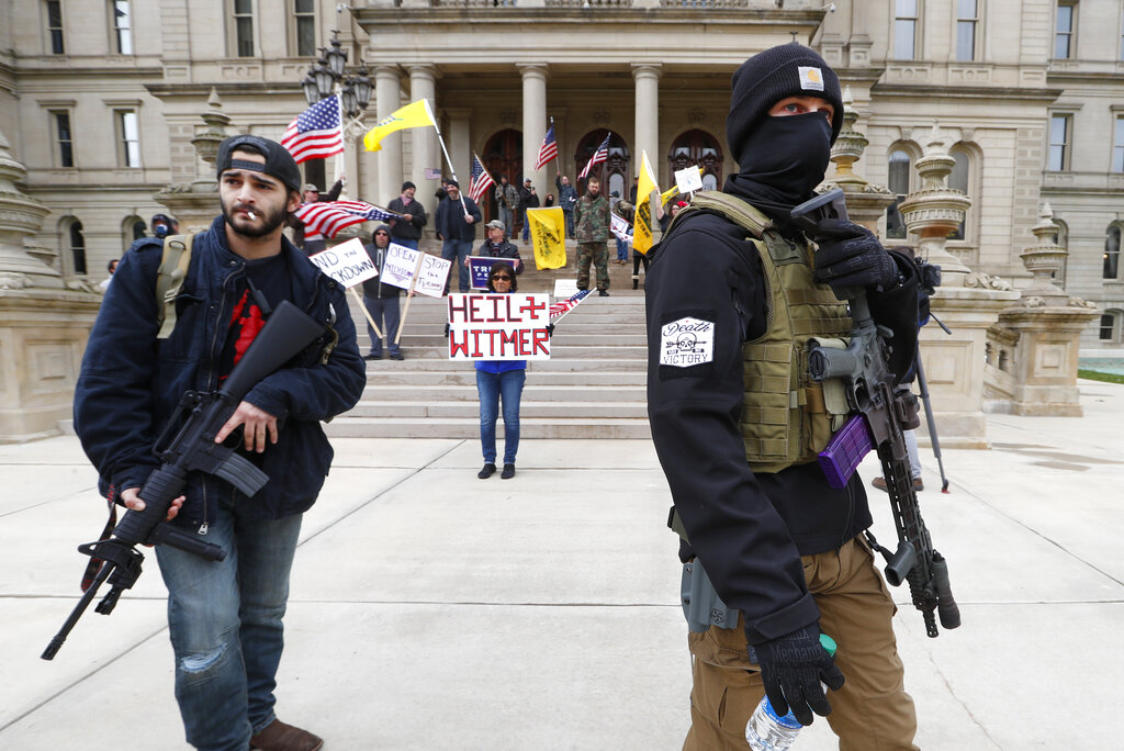 Protesters carry rifles near the steps of the Michigan State Capitol building in Lansing, Michigan on Wednesday. (AP Photo/Paul Sancya)