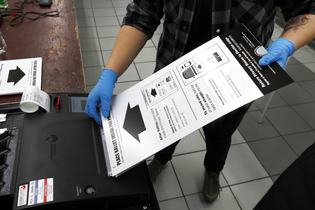 A poll worker wears rubber gloves as she enters a ballot in Chicago. A new poll from The Associated Press-NORC Center for Public Affairs Research finds Democrats are now much more likely than Republicans to support their state conducting elections exclusively by mail, 47% to 29%. (AP Photo/Charles Rex Arbogast, File)