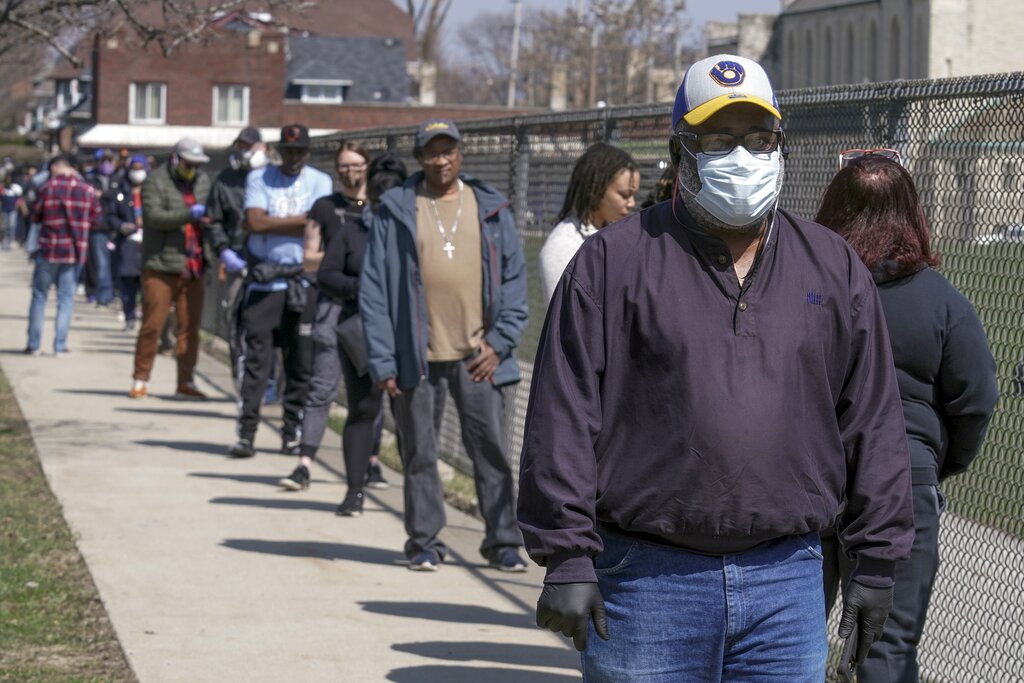 Voters observe social distancing guidelines as they wait to cast ballots at Washington High School in Milwaukee while ignoring a stay-at-home order to vote in the Wisconsin's presidential primary election on April 7th. (AP Photo/Morry Gash)