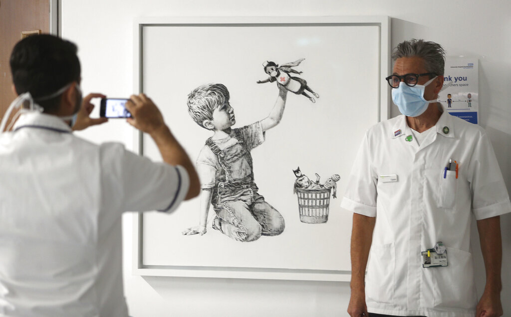 A staff member has their photo taken in front of the new artwork painted by Banksy during lockdown, entitled 'Game Changer', which has gone on display to staff and patients on Level C of Southampton General Hospital in Southampton, England. (Andrew Matthews/PA via AP)