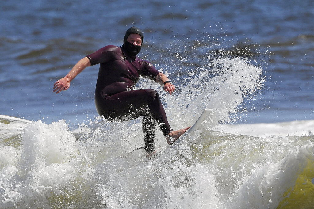 Tim O'Rourke surfs with a face covering to protect him from the coronavirus at Venice Beach, during the coronavirus outbreak in Los Angeles. Masks are required at Los Angeles County beaches, which reopened Wednesday to join counterparts in other states that have allowed a somewhat limited return to famed stretches of sand. (AP Photo/Mark J. Terrill, File)