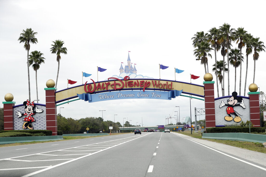 The road to the entrance of Walt Disney World has few cars Monday, March 16, 2020, in Lake Buena Vista, Fla. The Magic Kingdom, Epcot and Hollywood Studios were closed along with other theme parks around the state to help curb the spread of the coronavirus. (AP Photo/John Raoux)