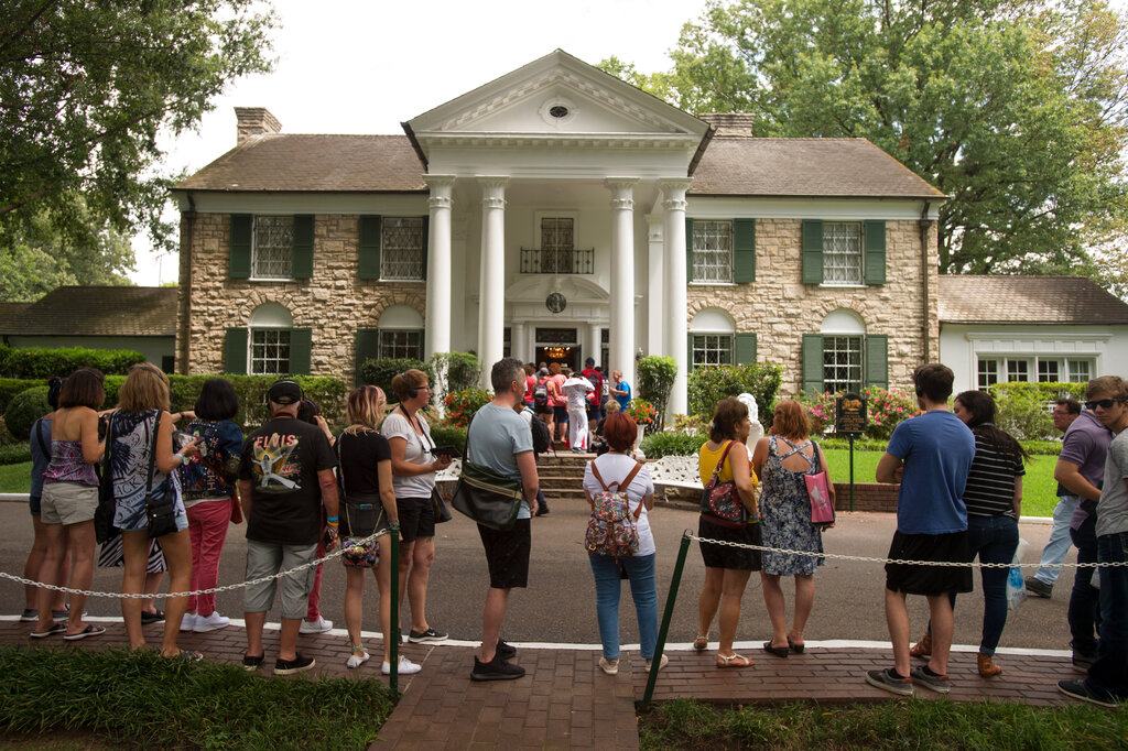 Fans wait in line outside Graceland, Elvis Presley's Memphis home, in 2017. Graceland says it will reopen Thursday, May 21, after it shut down tours and exhibits due to the new coronavirus outbreak. The tourist attraction in Memphis, Tennessee, said Sunday that it has adjusted its tours, and restaurant and retail operations, since it closed in March. (AP Photo/Brandon Dill, File)