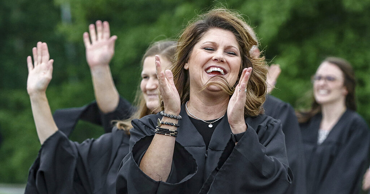 Daviess County High School teacher Krystal Phelps forms a line with fellow teachers, congratulating graduates as they exit the school after receiving diplomas, Monday, May 18, 2020, in Owensboro, Ky. Due to the coronavirus pandemic, and to practice social distancing rules, the graduation was conducted outside, with graduates arriving in vehicles, receiving diplomas, and immediately leaving the school property. (Greg Eans/The Messenger-Inquirer via AP)