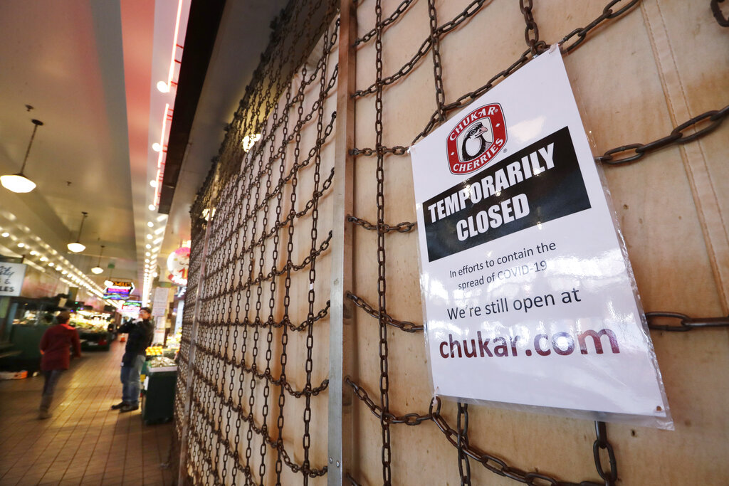 A sign explains the closure of a shop in the Pike Place Market in Seattle. (AP Photo/Elaine Thompson,File)