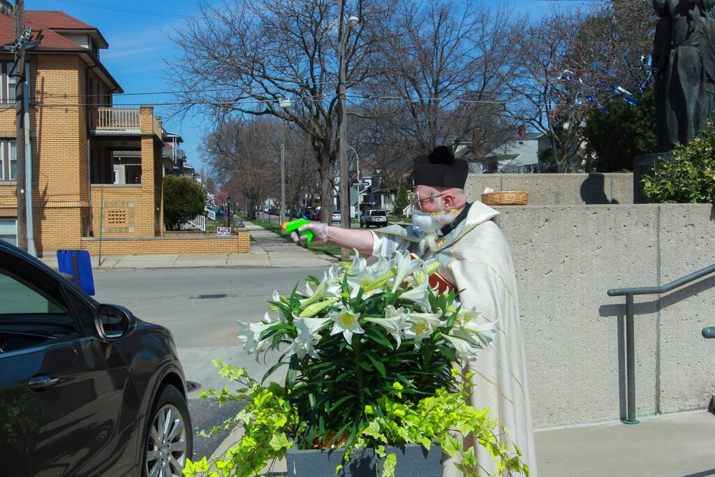 Rev. Timothy Pelc blesses Easter baskets outside St. Ambrose Church in Grosse Pointe Park, Mich. Pelc, wearing church vestments and protective gear, offering a prayer and sprayed holy water from a squirt gun instead of blessing baskets inside the church in a bid to maintain social distancing during the coronavirus pandemic. (Natalie White via AP)