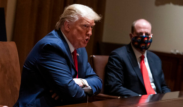 President Donald Trump speaks during a meeting with North Dakota Gov. Doug Burgum and Colorado Gov. Jared Polis, right, in the Cabinet Room of the White House, Wednesday, May 13, 2020, in Washington. (AP Photo/Evan Vucci)
