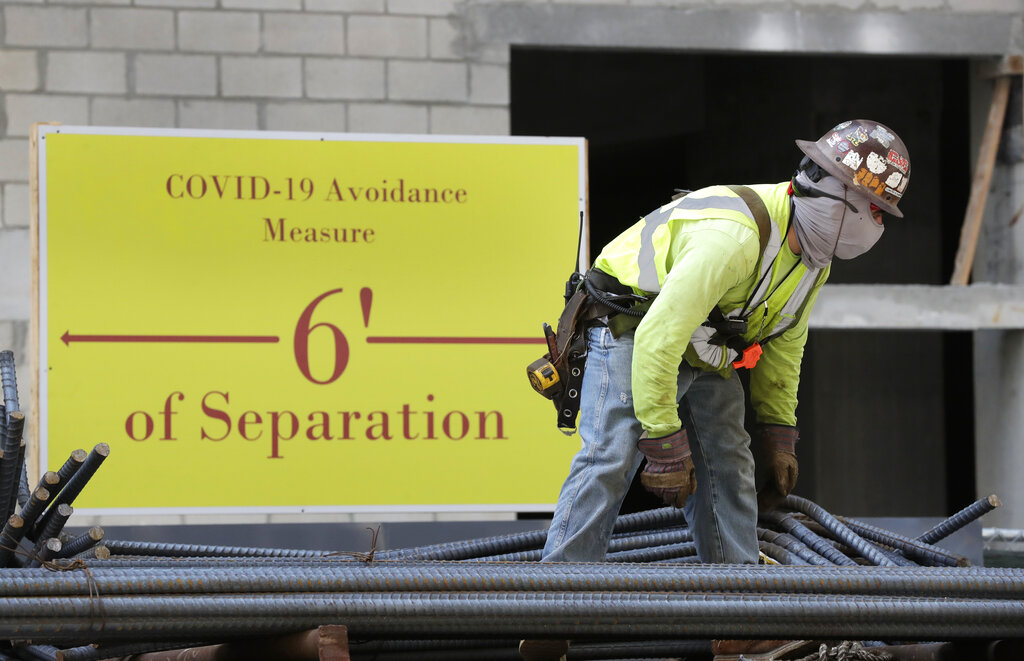 A construction worker wears a protective mask while standing in front of a sign reminding people to stay six feet apart in downtown Miami. (AP Photo/Wilfredo Lee)