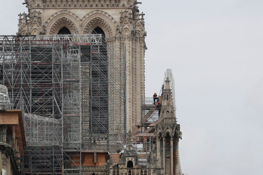 Workers remove scaffolding at Notre Dame cathedral on Monday in Paris. Workers suspended from ropes will be lowered into the charred remains of scaffolding that melted atop Notre Dame when the cathedral went up in flames and begin the delicate job of dismantling the 200 tons of metal. (AP Photo/Thibault