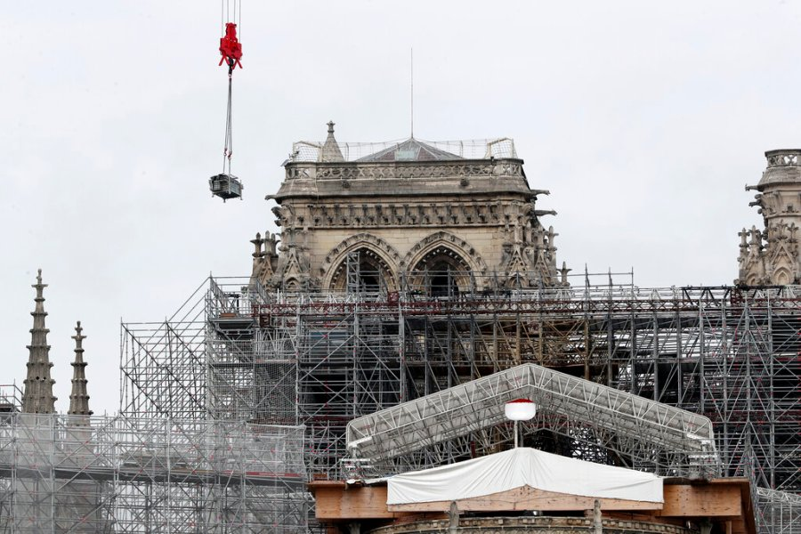 A crane removes scaffolding at Notre Dame cathedral in Paris. Workers suspended from ropes will be lowered into the charred remains of scaffolding that melted atop Notre Dame when the cathedral went up in flames and begin the delicate job of dismantling the 200 tons of metal. (AP Photo/Thibault Camus)