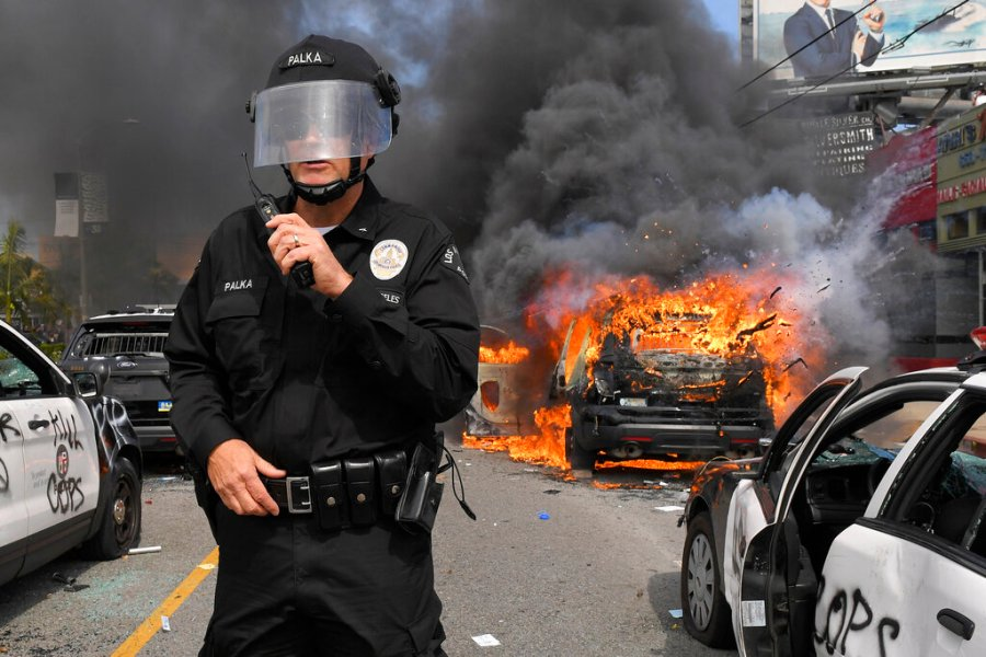 Los Angeles Police Department commander Cory Palka stands among several destroyed police cars as one burns during a protest over the death of George Floyd. (AP Photo/Mark J. Terrill)