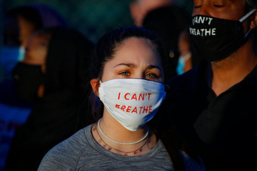 "Madeline Curry attends a protest with her father outside the Minneapolis 5th Police Precinct while wearing a protective mask that reads ""I CAN'T BREATHE"" on Saturday. (AP Photo/John Minchillo)"