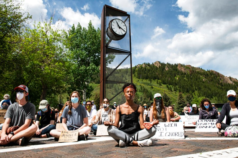 Jenelle Figgins, center, leads a moment of silent meditation before protesters march through the streets of Aspen, Colorado. (Kelsey Brunner/The Aspen Times via AP)
