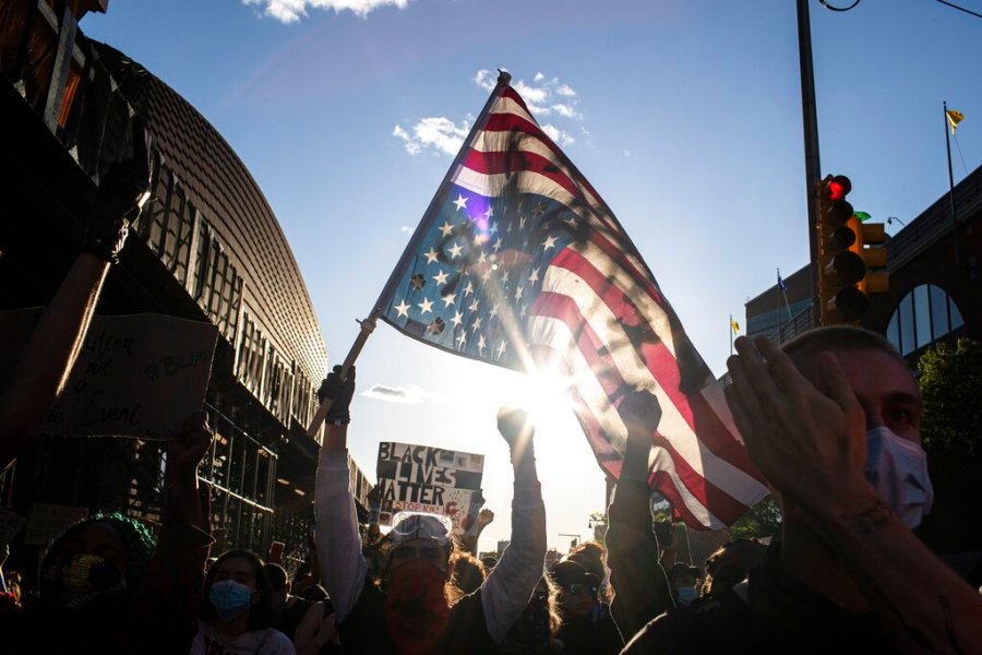 A man holds a U.S. flag upside down, a sign of distress, as protesters march down the street in the Brooklyn borough of New York. (AP Photo/Wong Maye-E)