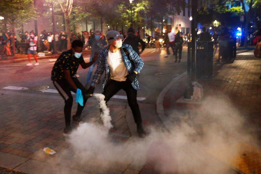 A protester tosses a smoke bomb towards police during a third night of unrest in Richmond, Va. The smoke bomb was ignited by a protester. (AP Photo/Steve Helber)
