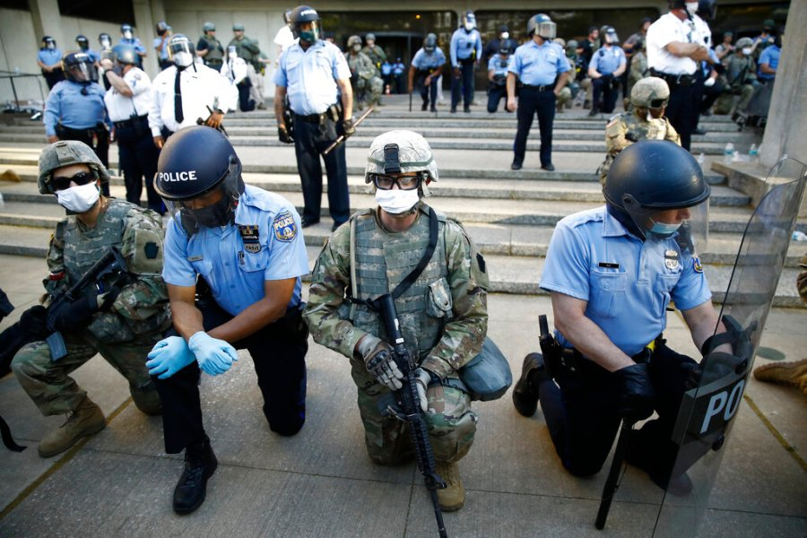 Philadelphia police and Pennsylvania National Guard take a knee at the suggestion of Philadelphia Police Deputy Commissioner Melvin Singleton, unseen, outside Philadelphia Police headquarters in Philadelphia, Monday, June 1, 2020 during a march calling for justice over the death of George Floyd, Floyd died after being restrained by Minneapolis police officers on May 25. (AP Photo/Matt Rourke)