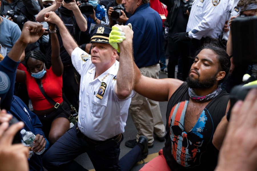 Chief of Department of the New York City Police, Terence Monahan, takes a knee with activists as protesters paused while walking in New York, Monday, June 1, 2020. Demonstrators took to the streets of New York to protest the death of George Floyd, who died May 25 after he was pinned at the neck by a Minneapolis police officer. (AP Photo/Craig Ruttle)