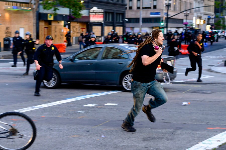 A man runs from police officers in Oakland, California on Monday. (AP Photo/Noah Berger)