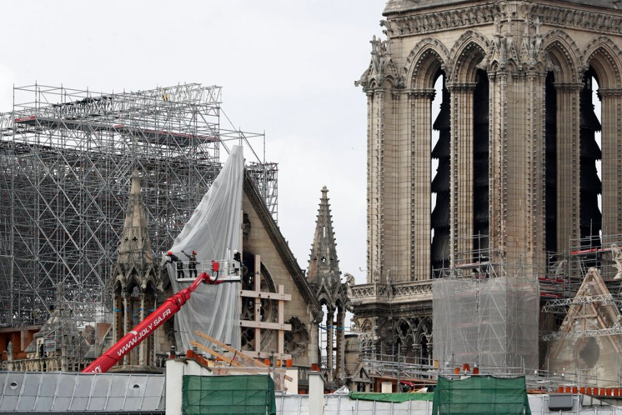 Workers remove scaffolding at Notre Dame cathedral in Paris. Workers suspended from ropes will be lowered into the charred remains of scaffolding that melted atop Notre Dame when the cathedral went up in flames and begin the delicate job of dismantling the 200 tons of metal. (AP Photo/Thibault Camus)