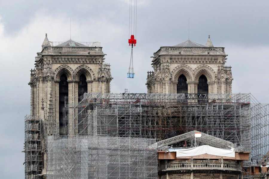 A box hangs from a crane at Notre Dame cathedral on Monday. Workers suspended from ropes will be lowered into the charred remains of scaffolding that melted atop Notre Dame when the cathedral went up in flames and begin the delicate job of dismantling the 200 tons of metal. (AP Photo/Thibault Camus)
