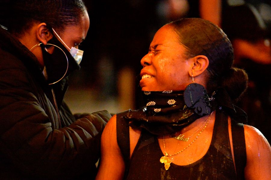 A protester squints after being sprayed with pepper spray during clashes with police in Boston. (Photo by JOSEPH PREZIOSO/AFP via Getty Images)