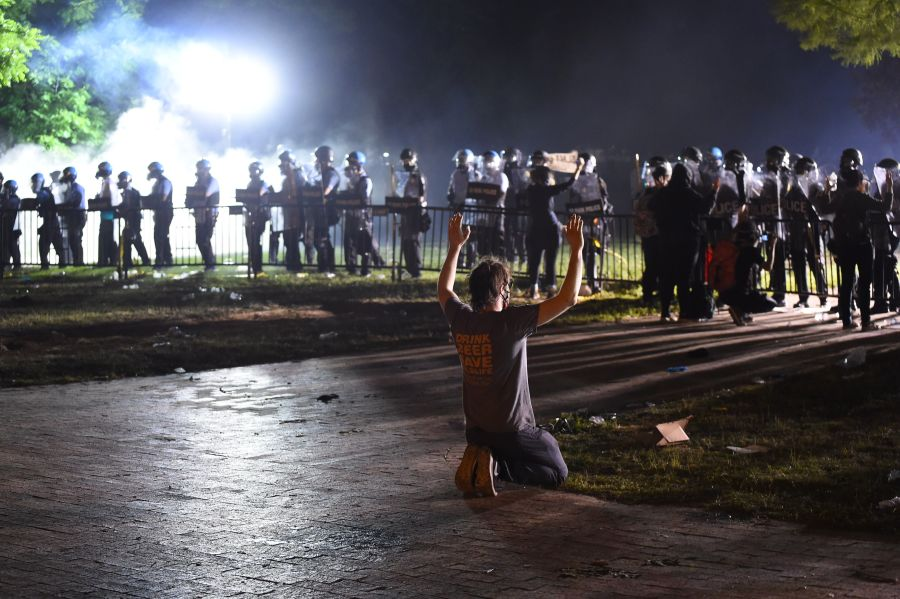A protester kneels and holds up his hands in front of a row of police during a demonstration near the White House. (Photo by ROBERTO SCHMIDT/AFP via Getty Images)