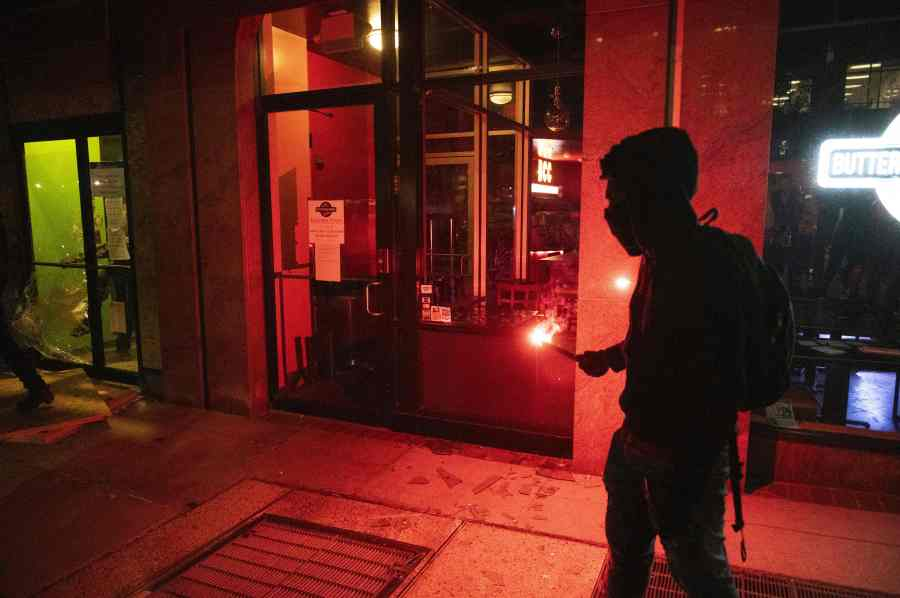 A person holds a burning flare near the entrance to a restaurant during a demonstration near the White House. (Photo by ROBERTO SCHMIDT/AFP via Getty Images)