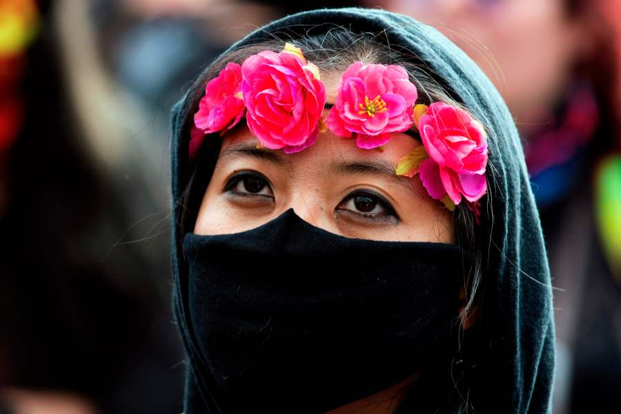 A demonstrator wears a ring of roses along with a face mask during a protest in Denver. (Photo by JASON CONNOLLY/AFP via Getty Images)
