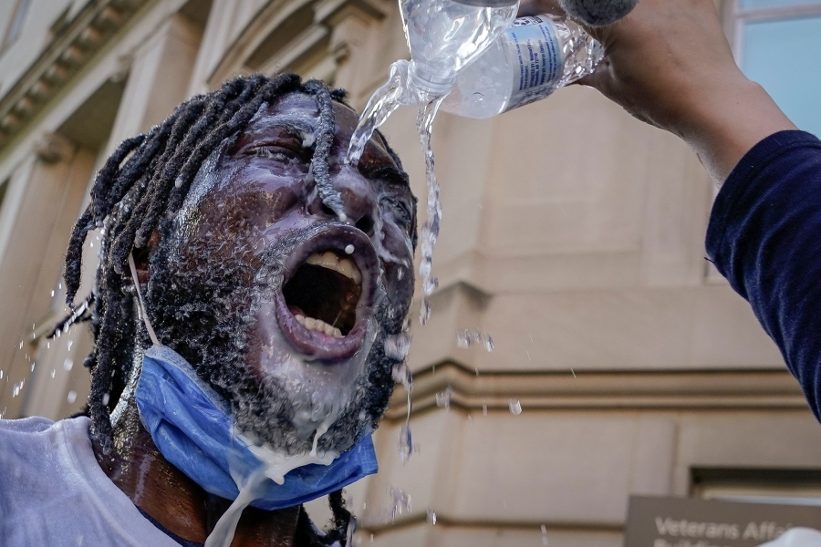A demonstrator is doused with water and milk after being hit with pepper spray during a protest on June 1, 2020 in downtown Washington, DC. (Photo by Drew Angerer/Getty Images)