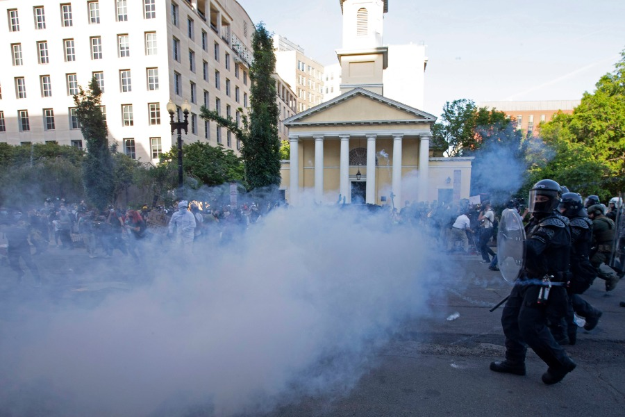 Police officers wearing riot gear push back demonstrators next to St. John's Episcopal Church outside of the White House. (Photo by JOSE LUIS MAGANA/AFP via Getty Images)