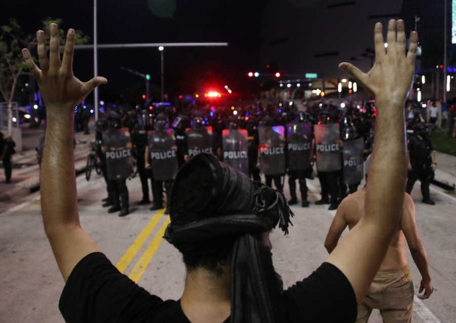 Police watch as demonstrators block a roadway while protesting against police brutality and the death of George Floyd in Miami, Florida. (Photo by Joe Raedle/Getty Images)