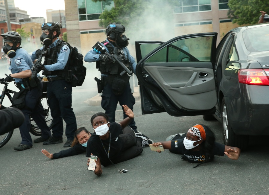 Police remove people from a vehicle during a protest against police brutality and the death of George Floyd in Minneapolis, Minnesota. (Photo by Scott Olson/Getty Images)