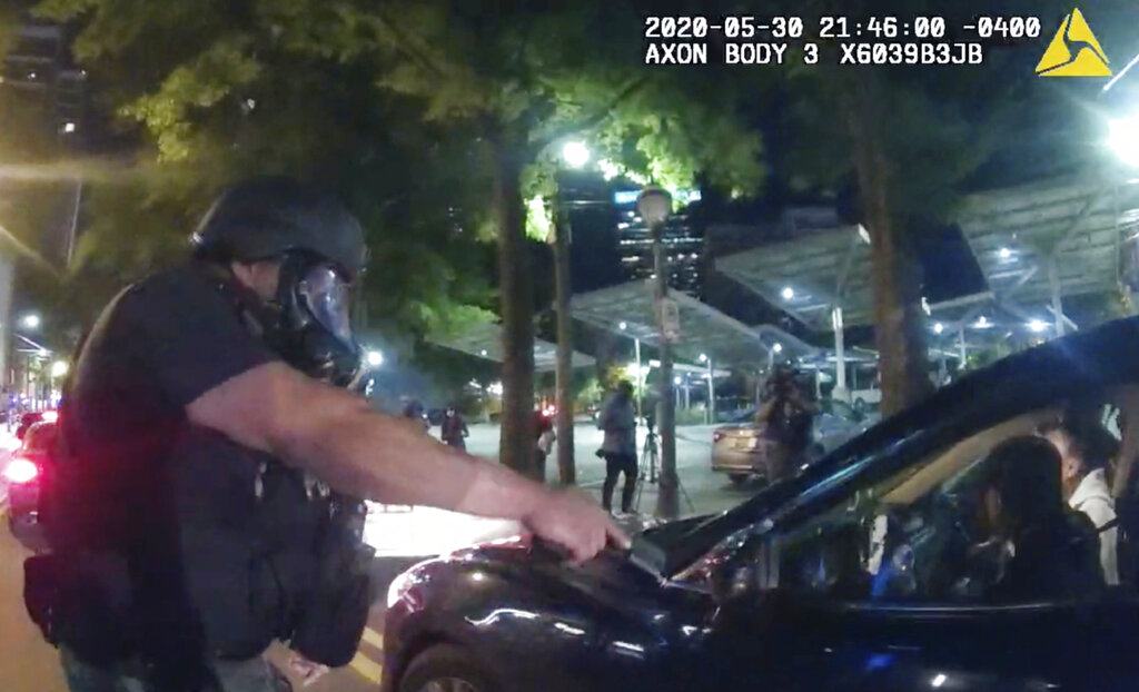 In body camera video released by the Atlanta Police Department, an officer points his handgun at Messiah Young while the college student is seated in his vehicle, in Atlanta.  (Atlanta Police Department via AP)