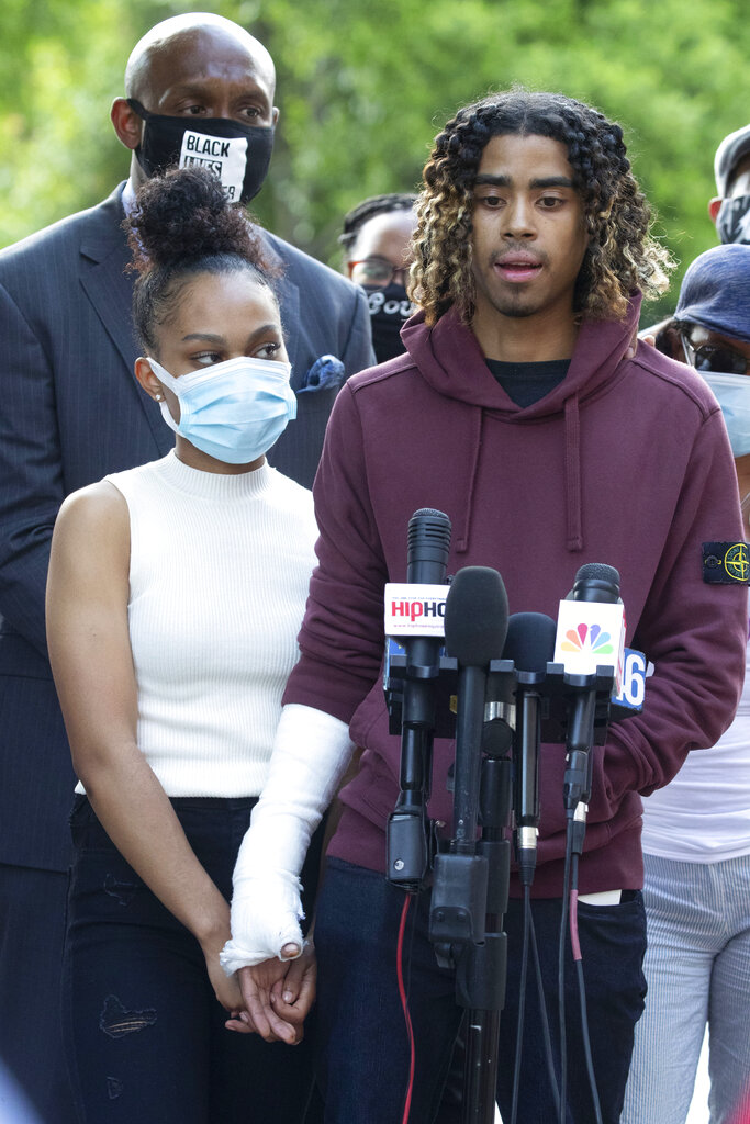 Taniyah Pilgrim holds Messiah Young's bandaged hand as he speaks during a news conference on the campus of Morehouse College. (AP Photo/John Bazemore)
