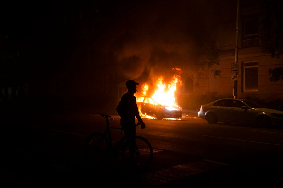 A demonstrator watches a car burn near the White House in Washington. (AP Photo/Evan Vucci)