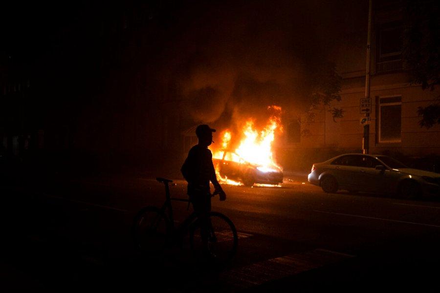 A demonstrator watches a car burn near the White House in Washington. (AP Photo/Evan Vucci)