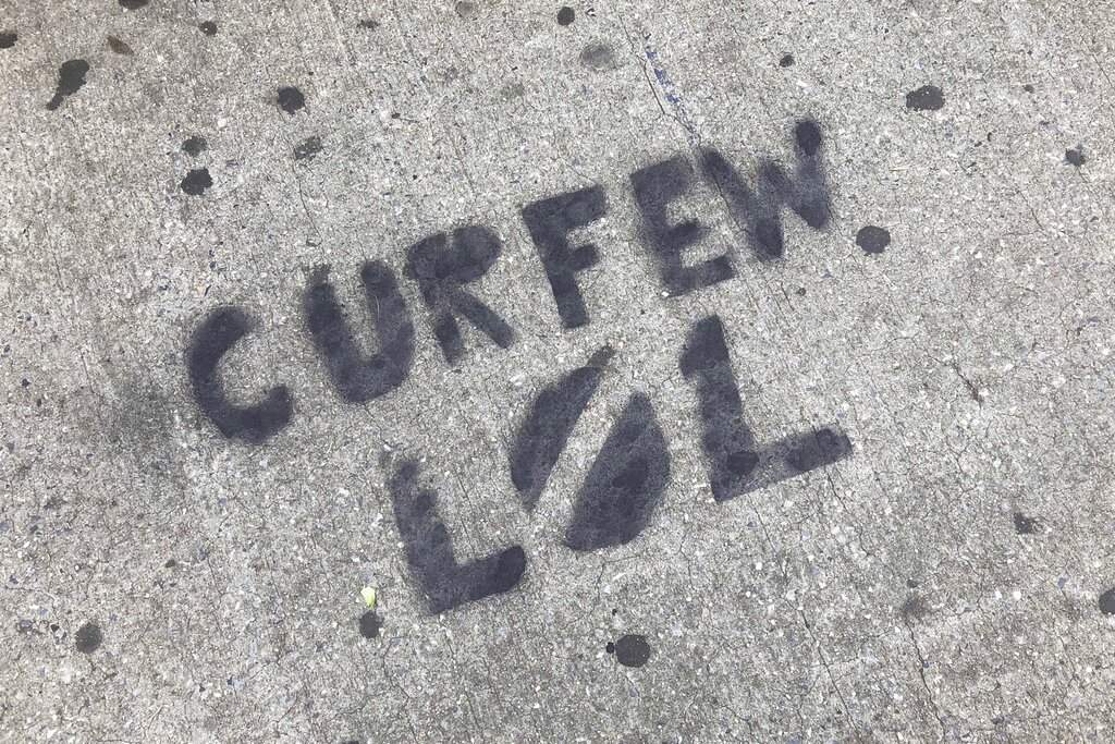 A sidewalk is spray painted with graffiti about New York City's curfew order in Brooklyn on Tuesday. (AP Photo/Mark Lennihan)
