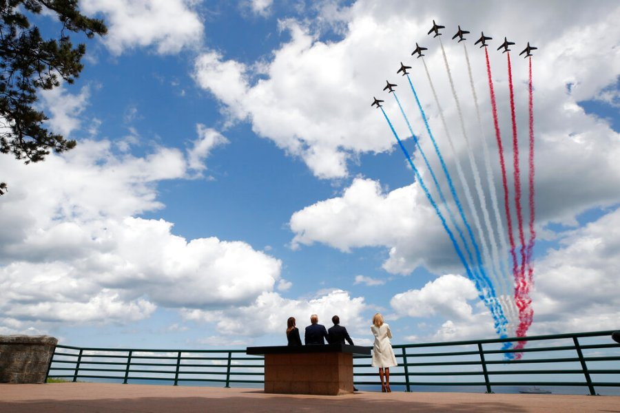 In this June 6, 2019 file photo, President Donald Trump, first lady Melania Trump, French President Emmanuel Macron and Brigitte Macron, watch a flyover during a ceremony to commemorate the 75th anniversary of D-Day at the American Normandy cemetery, in Colleville-sur-Mer, Normandy, France. In sharp contrast to the 75th anniversary of D-Day, this year's 76th will be one of the loneliest remembrances ever, as the coronavirus pandemic is keeping nearly everyone from traveling. (AP Photo/Alex Brandon, File)