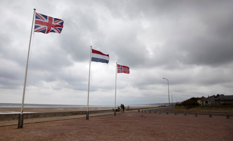 In this photo taken on Thursday, June 4, 2020, two people stop to look at an information board at Omaha Beach in Saint-Laurent-sur-Mer, Normandy, France. In sharp contrast to the 75th anniversary of D-Day, this year's 76th will be one of the loneliest remembrances ever, as the coronavirus pandemic is keeping nearly everyone from traveling. (AP Photo/Virginia Mayo)