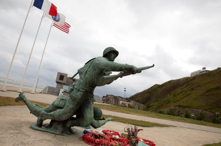 In this photo taken on Thursday, June 4, 2020, wreaths and flags sit in front of the Ever Forward memorial near Omaha Beach, in Vierville-sur-Mer, Normandy, France. In sharp contrast to the 75th anniversary of D-Day, this year's 76th will be one of the loneliest remembrances ever, as the coronavirus pandemic is keeping nearly everyone from traveling. (AP Photo/Virginia Mayo)