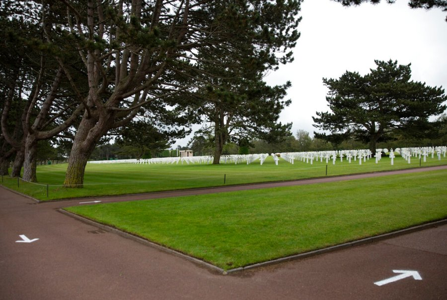 Arrows are painted on the ground to guide visitors to walk only one way, to prevent the spread of the coronavirus, at the Normandy American Cemetery in Colleville-sur-Mer, Normandy, France. In sharp contrast to the 75th anniversary of D-Day, this year's 76th will be one of the loneliest remembrances ever, as the coronavirus pandemic is keeping nearly everyone from traveling. (AP Photo/Virginia Mayo)