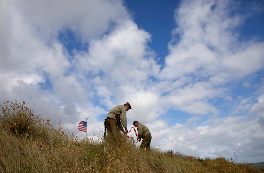 Two men in WWII period uniforms mark off an area in a dune overlooking Omaha Beach prior to a ceremony at the Charles Shay Memorial in Saint-Laurent-sur-Mer, Normandy, France, Friday, June 5, 2020. Saturday's anniversary of D-Day will be one of the loneliest remembrances ever, as the coronavirus pandemic is keeping almost everyone away, from government leaders to frail veterans who might not get another chance for a final farewell to their unlucky comrades. (AP Photo/Virginia Mayo)