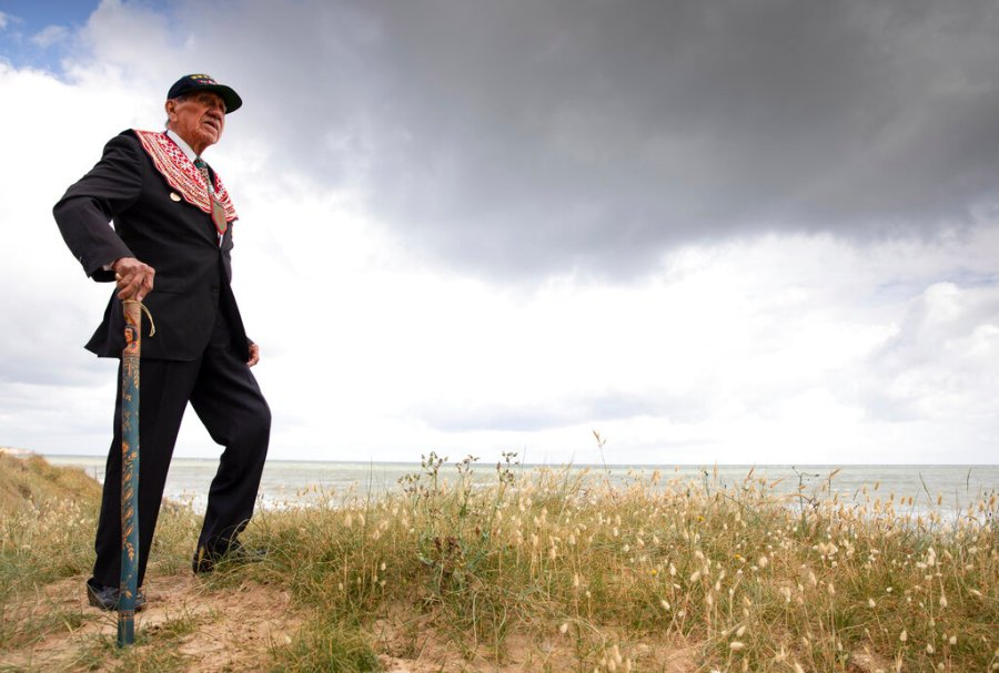 World War II D-Day veteran and Penobscot Elder from Maine, Charles Norman Shay, poses on the dune overlooking Omaha Beach prior to a ceremony in Saint-Laurent-sur-Mer, Normandy, France. Saturday's anniversary of D-Day will be one of the loneliest remembrances ever, as the coronavirus pandemic is keeping almost everyone away, from government leaders to frail veterans who might not get another chance for a final farewell to their unlucky comrades. (AP Photo/Virginia Mayo)
