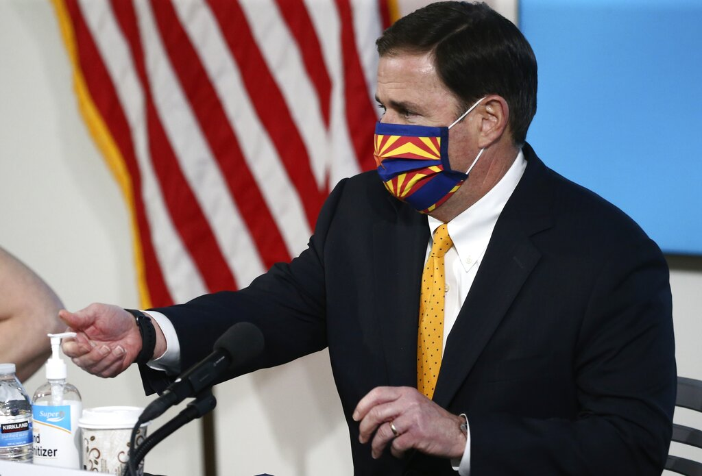 Arizona Republican Gov. Doug Ducey uses hand sanitizer and wears a face mask prior to speaking about the latest coronavirus data at a news conference Thursday in Phoenix. (AP Photo/Ross D. Franklin, Pool)