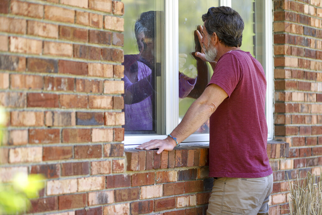 Jack Campise talks with his mother, Beverly Kearns, through her apartment window at the Kimberly Hall North nursing home in Windsor, Conn. The coronavirus has had no regard for health care quality or ratings as it has swept through nursing homes around the world, killing efficiently even in highly rated care centers. Preliminary research indicates the numbers of nursing home residents testing positive for the coronavirus and dying from COVID-19 are linked to location and population density — not care quality ratings. (AP Photo/Chris Ehrmann
