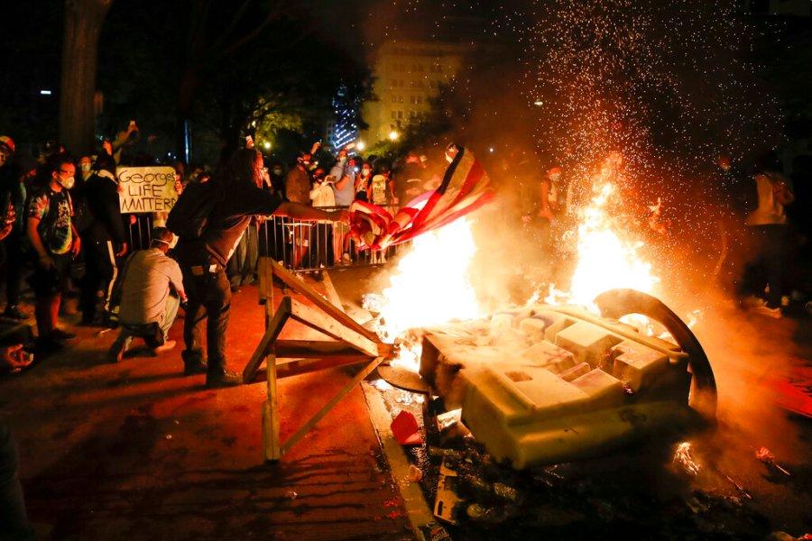Demonstrators start a fire near the White House. (AP Photo/Alex Brandon)