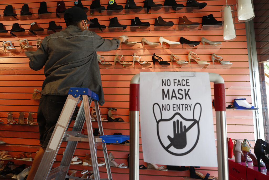 Manager Angel Ramos arranges shoes on a display in Top shoes in the Brooklyn borough of New York City, after retail stores were allowed to reopen to customers. In a city famous for its lack of patience, some businesses have jumped ahead on what's supposed to be a slow and methodical emergence from coronavirus lockdown. (AP Photo/Kathy Willens)
